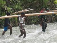 Babinsa Ransiki, Seberangkan Anak di Sungai Berarus Deras